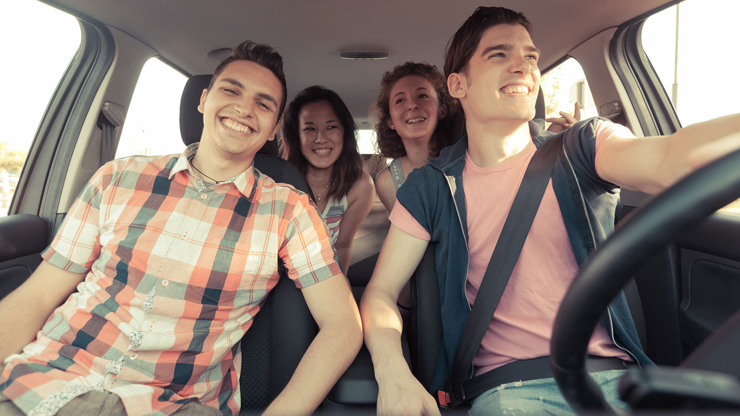 four happy people in car