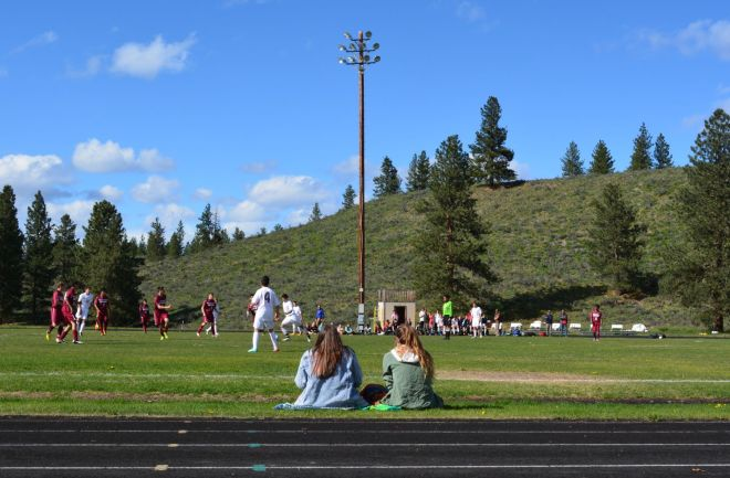 Students at Liberty Bell High School watch a soccer game against the Okanogan High School team.