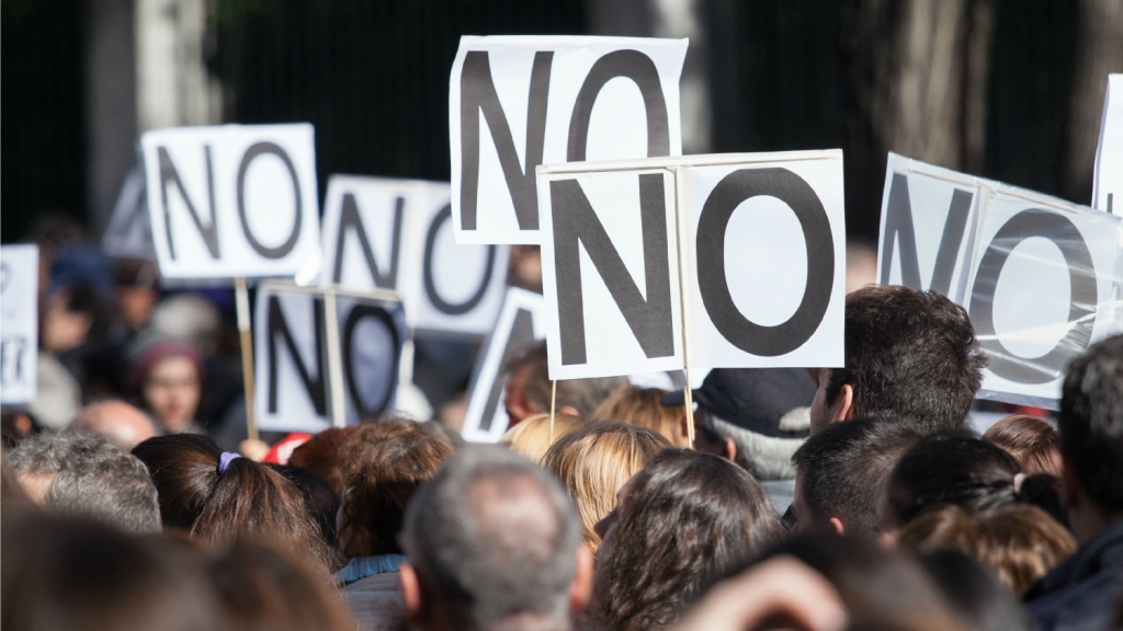 "protesters holding ""no"" signs"