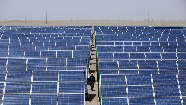 A Chinese worker walks in the solar modules of a newly installed 100MW photovoltaic on-grid power project on July 21, 2010 in Dunhuang of China's northwest Gansu Province.