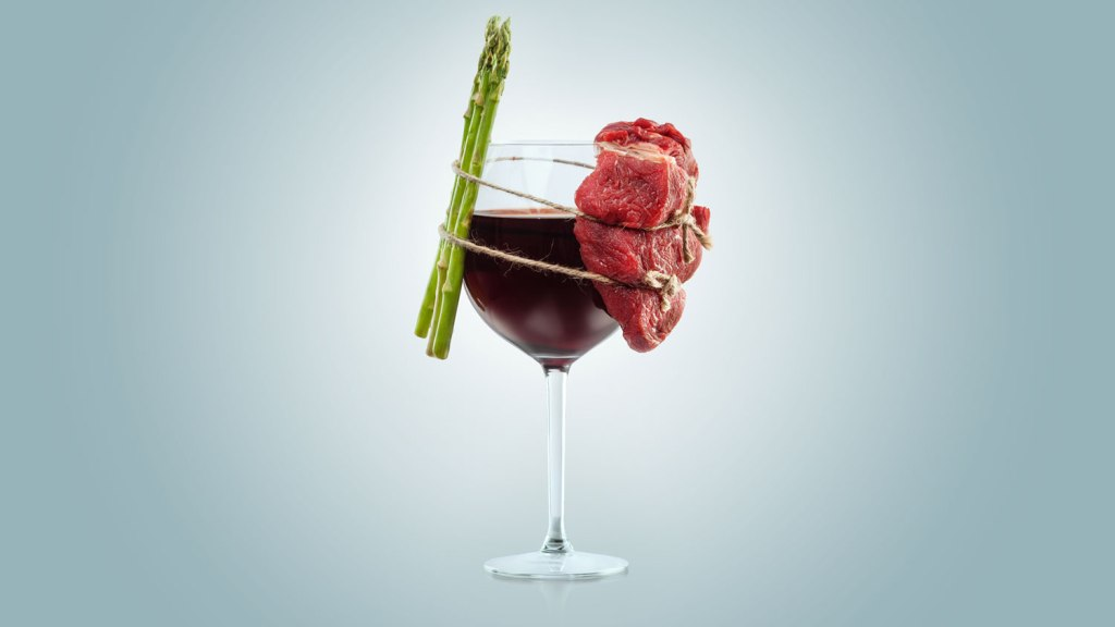 wine glass with asparagus and red meat