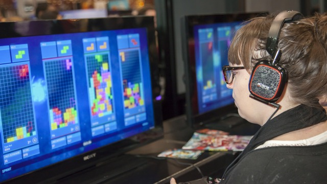 Comic Con attendee plays Tetris Ultimate during Comic Con 2014 at The Jacob K. Javits Convention Center in New York City