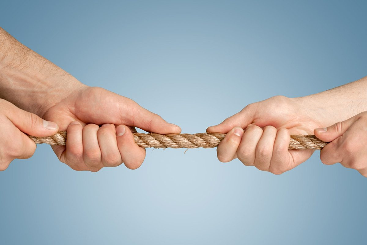 Two people in a tug-of-war match, illustraiting how it can often feel when arguing with a climate skeptic