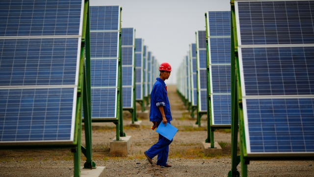 Chinese worker and solar panels
