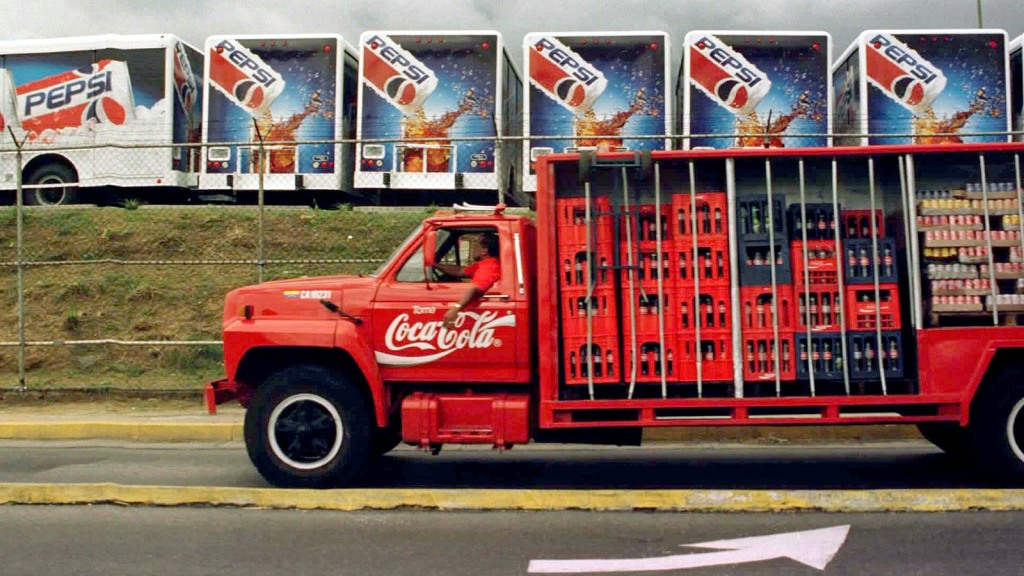 A Coca Cola truck passes in front of a Pepsi Co. parking lot filled with new Pepsi Cola trucks