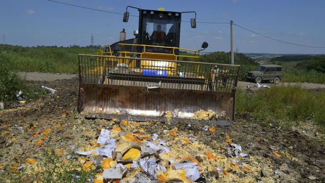 An employee operates a bulldozer while destroying illegally imported food falling under restrictions in Belgorod region, Russia, August 6, 2015