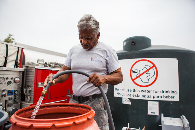Reuben Perez fills up a barrel of water at the public tank to bring to Juana Garcia's home. The water will be used to do laundry, take bucket showers, and flush the toilet.