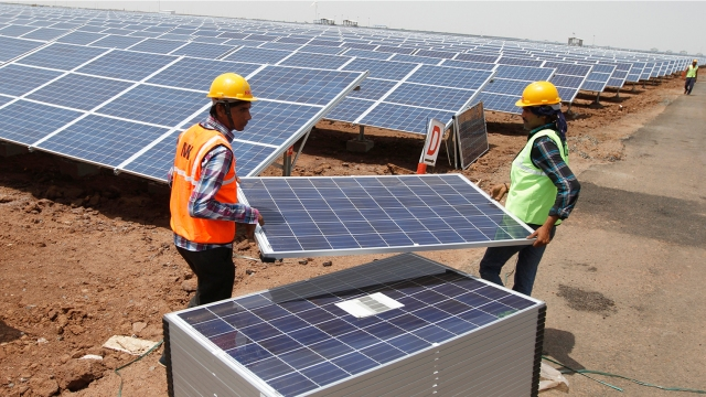 Workers carry photovoltaic solar panels