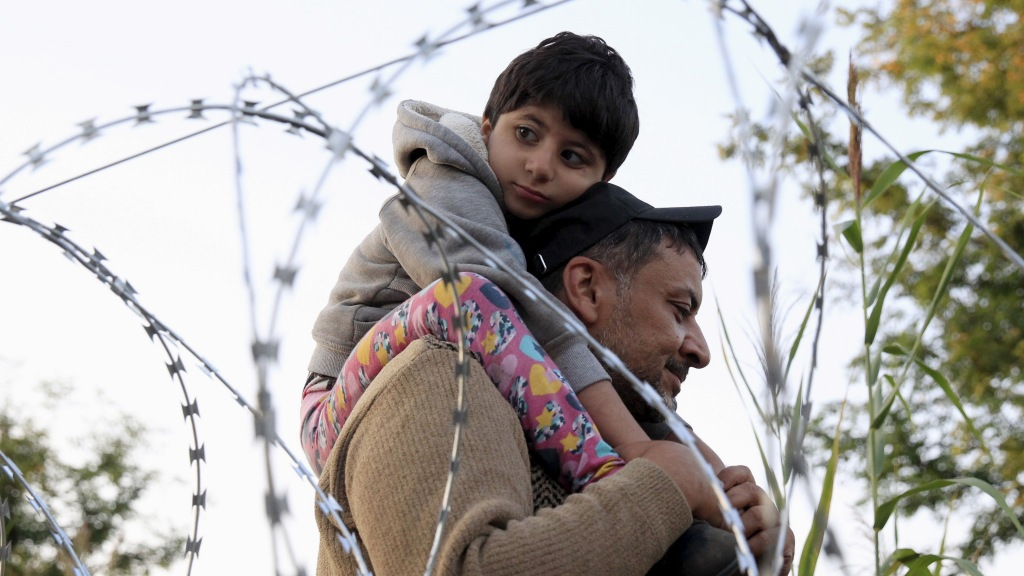A Syrian migrant with a boy, on the Serbian side of the border with Hungary, walks behind a razor wire near Roszke, Hungary August 28, 2015.