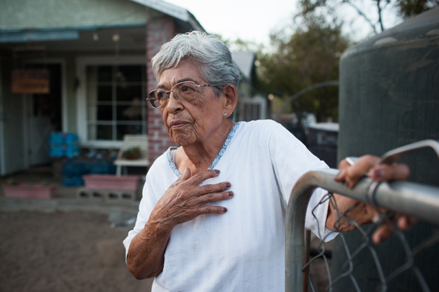 Vicky Yorba, 95, stands beside the water tank in her front yard.