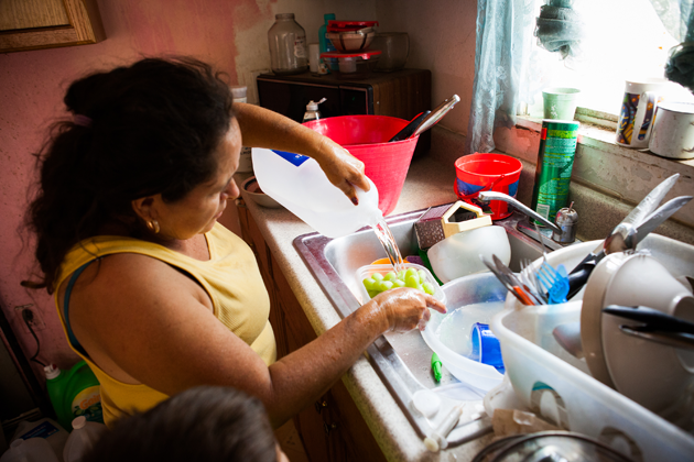 Juana Garcia washes grapes with bottled water. She soaks dirty dishes in soapy water before rinsing them to minimize water use.