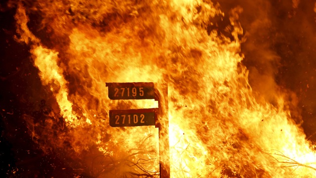 Flames from the Jerusalem Fire consume a sign containing addresses to homes along Morgan Valley Road in Lake County, California
