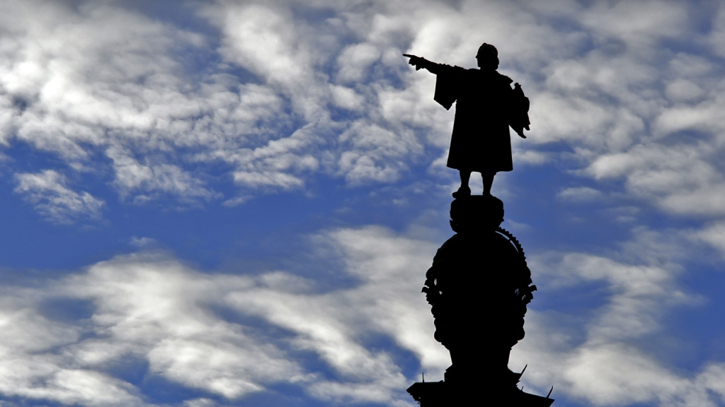A silhouetted Christopher Columbus statue