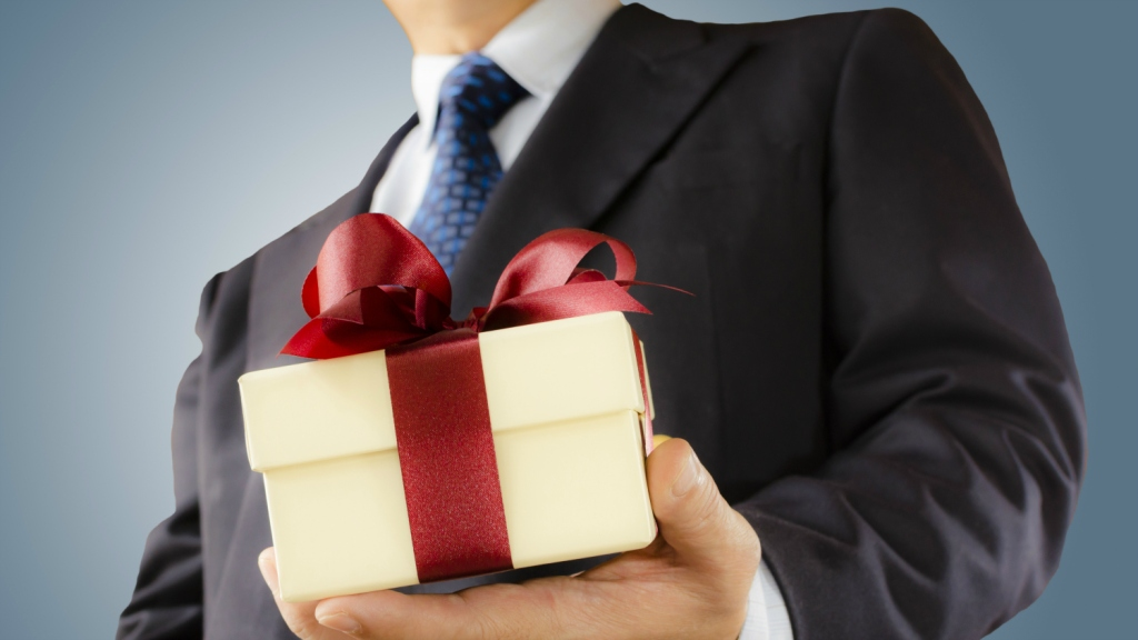 suited man offering gift