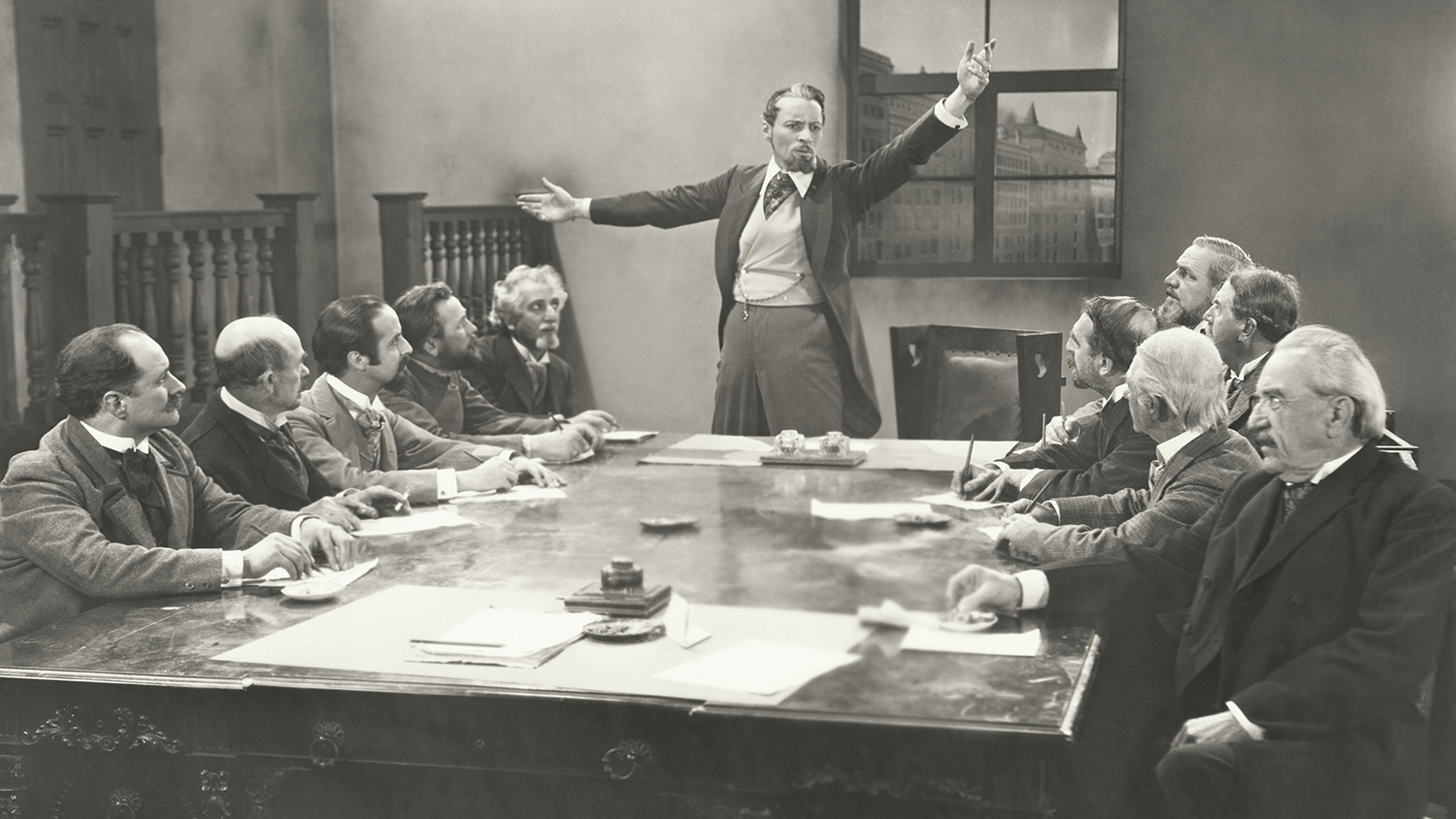 Man in a waistcoat talking to a committee of similarly dressed old white men