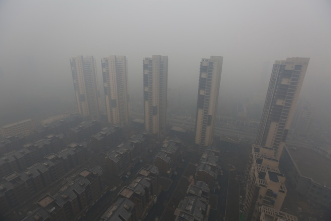 Residential buildings are seen shrouded in haze in Shenyang, Liaoning province, Nov. 8, 2015.