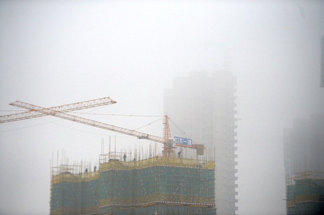 A construction site is seen covered in smog in Jinan, Shandong province, China, November 10, 2015.