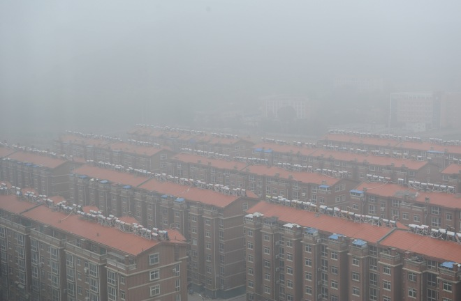 Residential buildings are seen surrounded in smog in Jinan, Shandong province, China, November 10, 2015.