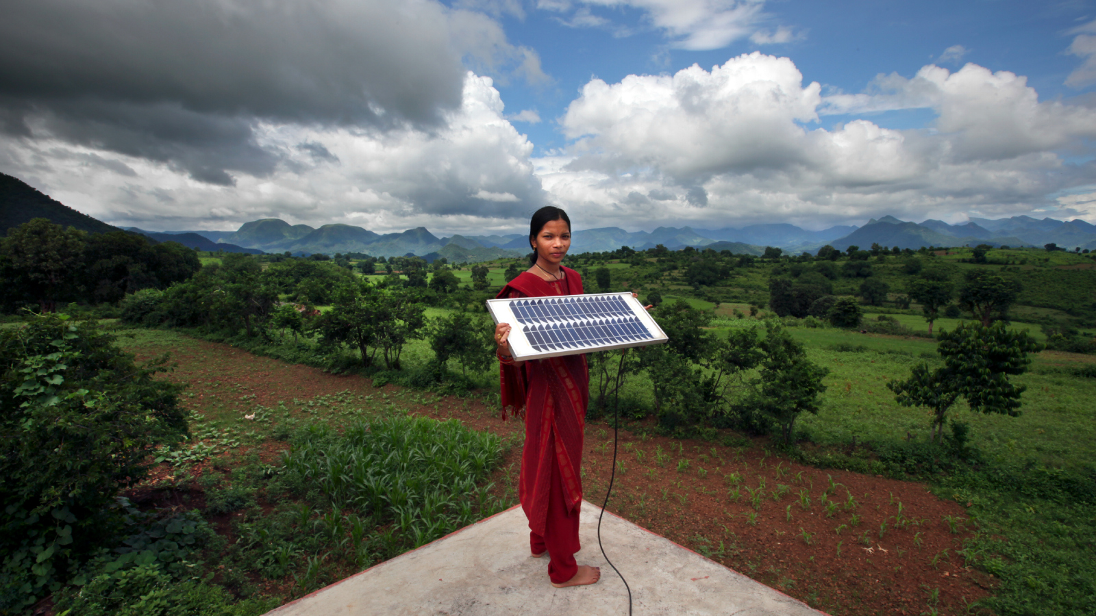 Indian woman on roof with solar module