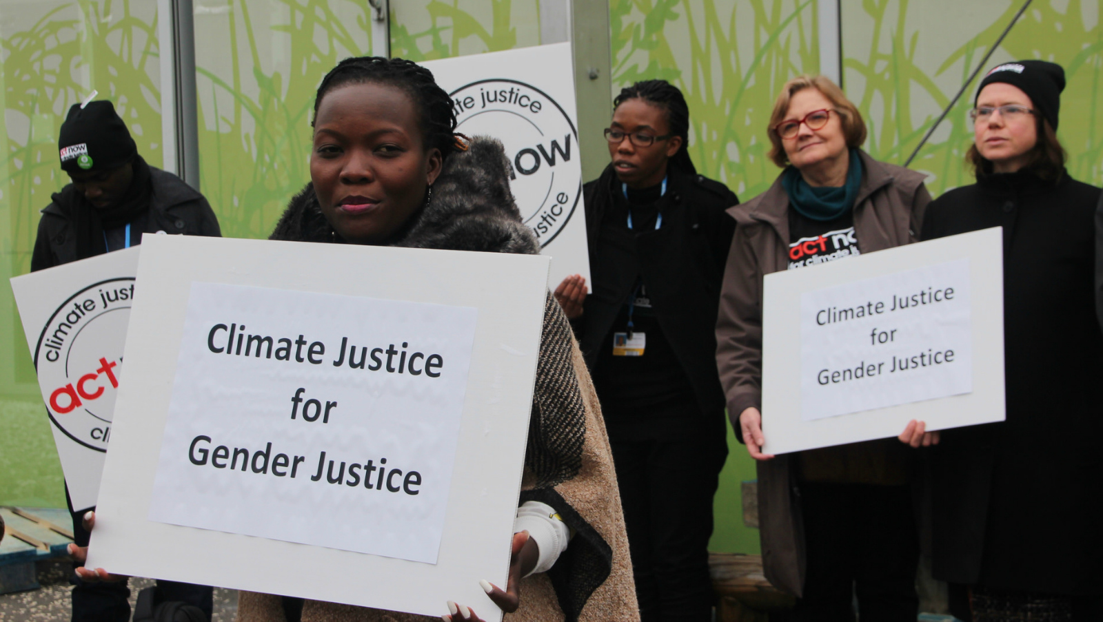 "activists with signs: ""climate justice for gender justice"""