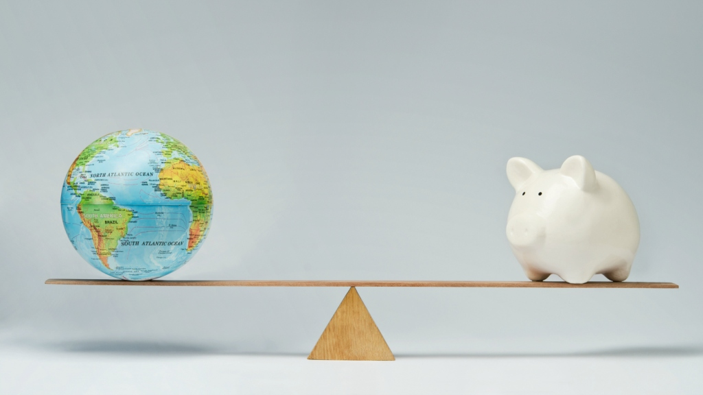 globe and piggy bank on seesaw