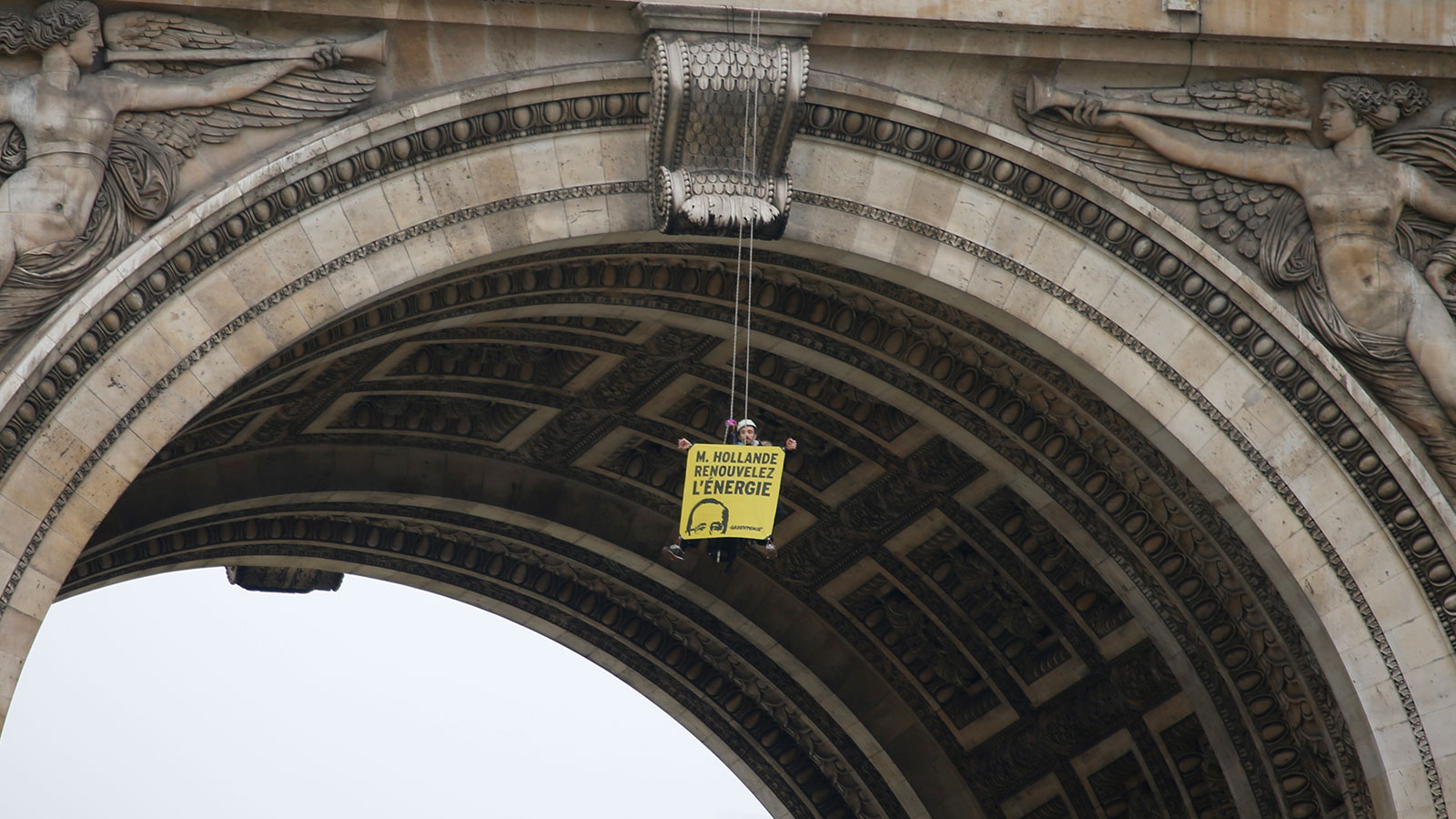 "A Greenpeace activist hangs with a banner reading ""Mister Hollande, renew energy"" from the top of the Arc de Triomphe during a protest on the Champs Elysees avenue in Paris, France, December 11, 2015 as part of the World Climate Change Conference 2015 (COP21)."