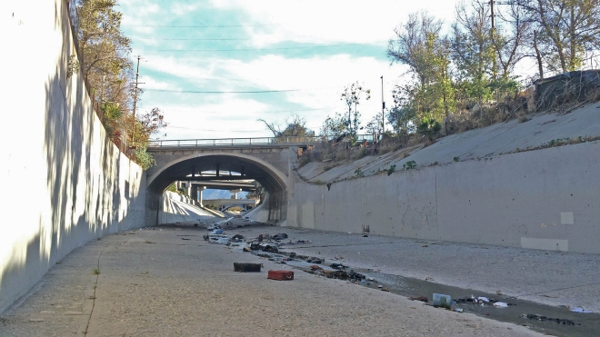 A large encampment dots the top of the top of the banks of the Arroyo Seco in Lincoln Heights, Calif.