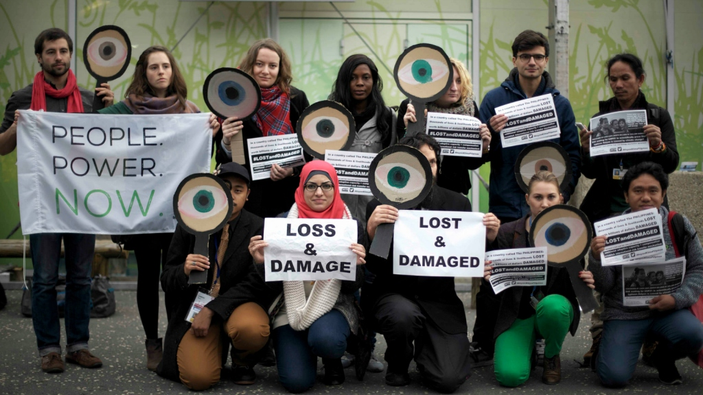 "protesters with ""loss and damage"" signs"