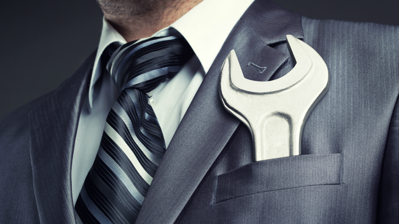 suited man with wrench in pocket