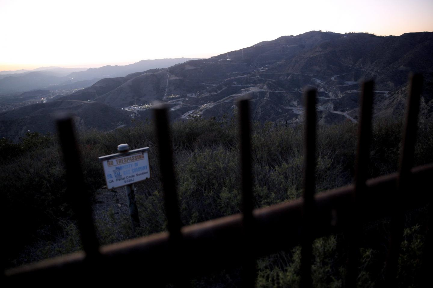 "A ""No Trespassing"" sign and fence mark the boundary of the SoCalGas Aliso Canyon Storage Facility, looking toward where a leaking gas well and a relief well are being drilled. Public trails crisscross the hills near the well where the smell of gas was strong on Dec. 30, 2015."