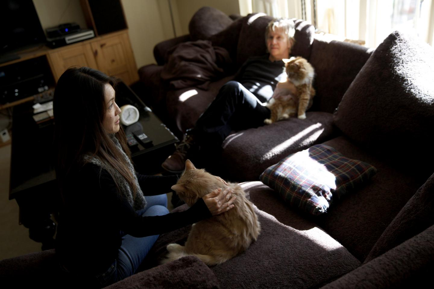 Co-founders of Save Porter Ranch Kyoko Hibino, left, and Matt Pakucko sit on their couch with their cats. The pair are trying to raise awareness of the nearly three-month-old gas leak and urge lawmakers to act.