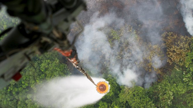 A helicopter drops water to extinguish a fire at a plantation in Kubu Raya district, Indonesia
