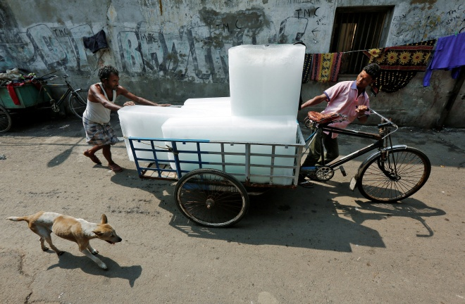 Men transport ice on a tricycle to a local market in Kolkata, India May 24, 2016. REUTERS/Rupak De Chowdhuri - RTSFN2B
