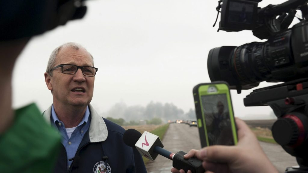 U.S. Representative Kevin Cramer, (R-ND) speaks to the media while smoke from the wreckage of several oil tanker cars that derailed in a field near the town of Heimdal, North Dakota billows behind him May 6, 2015. A train carrying crude oil derailed and caught fire on Wednesday, officials said, just days after the U.S. government announced sweeping reforms to improve safety of the volatile shipments.