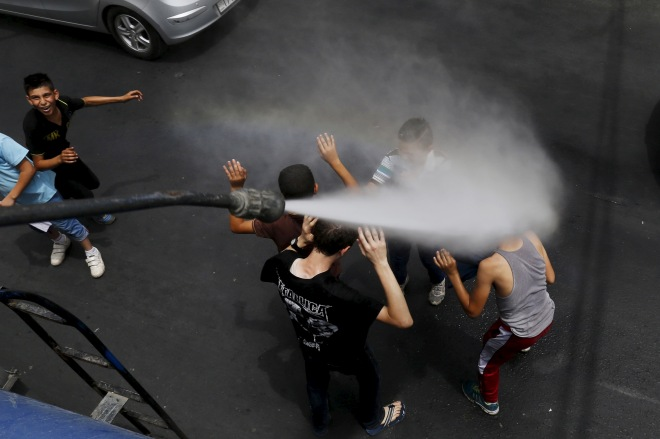 Children react as Greater Amman Municipality personnel spray them with a water sprinkler in order to cool them down as part of measures to ease the effect of a heatwave, in Amman, Jordan, August 3, 2015. REUTERS/Muhammad Hamed - RTX1MV71