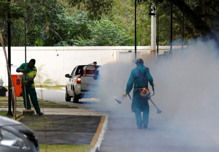 A truck sprays insecticide near grounds workers at Olympic media accommodations as part of preventative measures against the Zika virus.