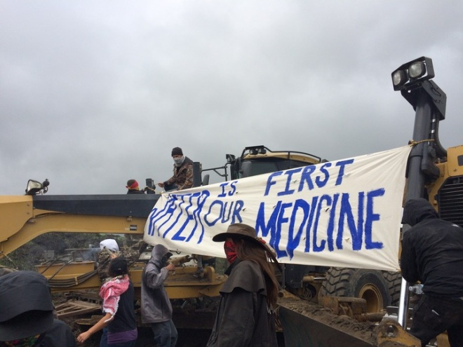 Activists swarmed a Dakota Access construction site on Tuesday morning, unfurling banners and leading several dozen people, including Green Party presidential candidate Jill Stein, in song and prayer. Law enforcement officers stood back and observed the scene as two activists chained themselves to excavators; construction workers vacated the site without comment.
