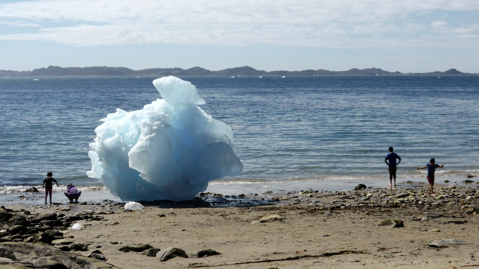 Children play next to icebergs on the beach in Nuuk, Greenland.