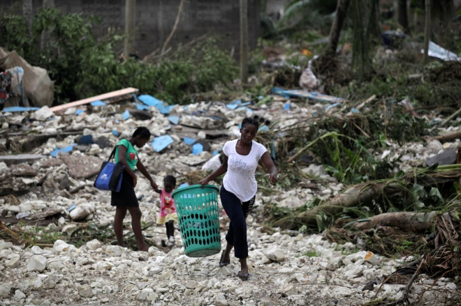 A woman carries a laundry basket in an area devastated by Hurricane Matthew in Cavaillon, Haiti, October 6, 2016. REUTERS/Andres Martinez Casares - RTSR4LS