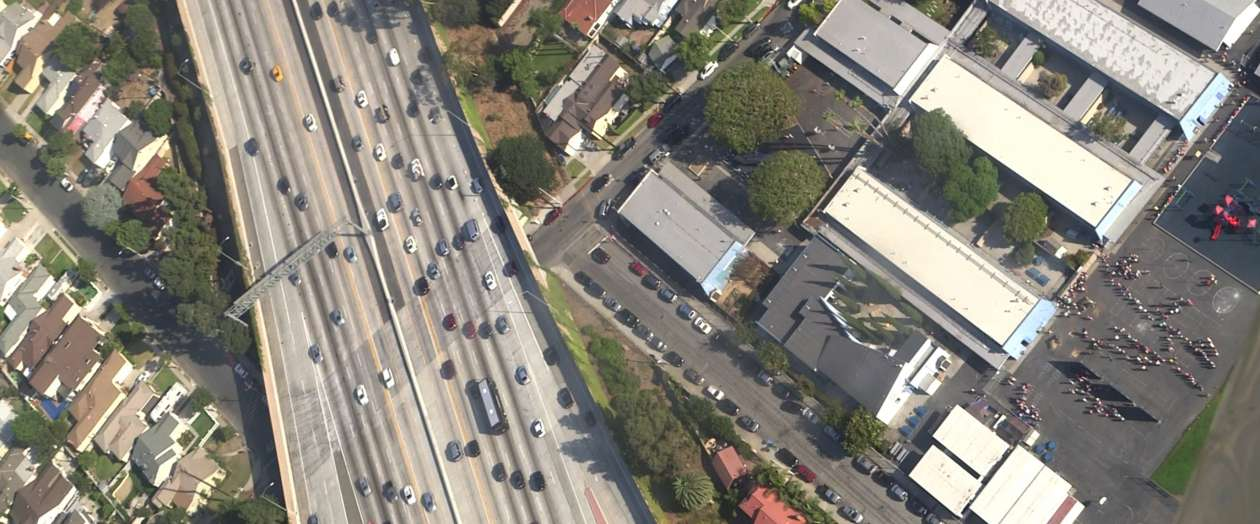 Students line up outside El Marino Language School as vehicles zoom by on Interstate 405 in Culver City, California.