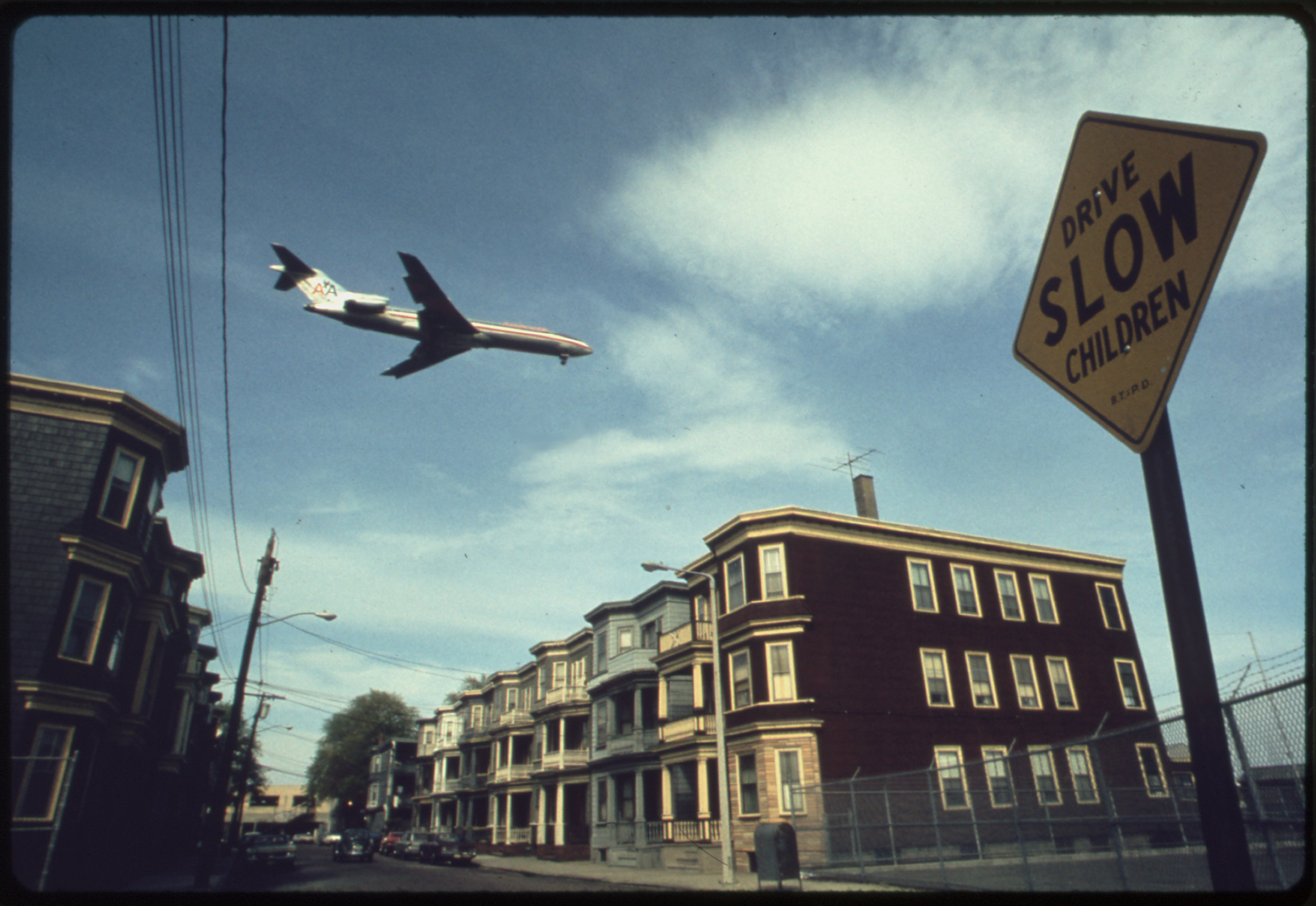 An airplane flies over houses in Boston in 1973.