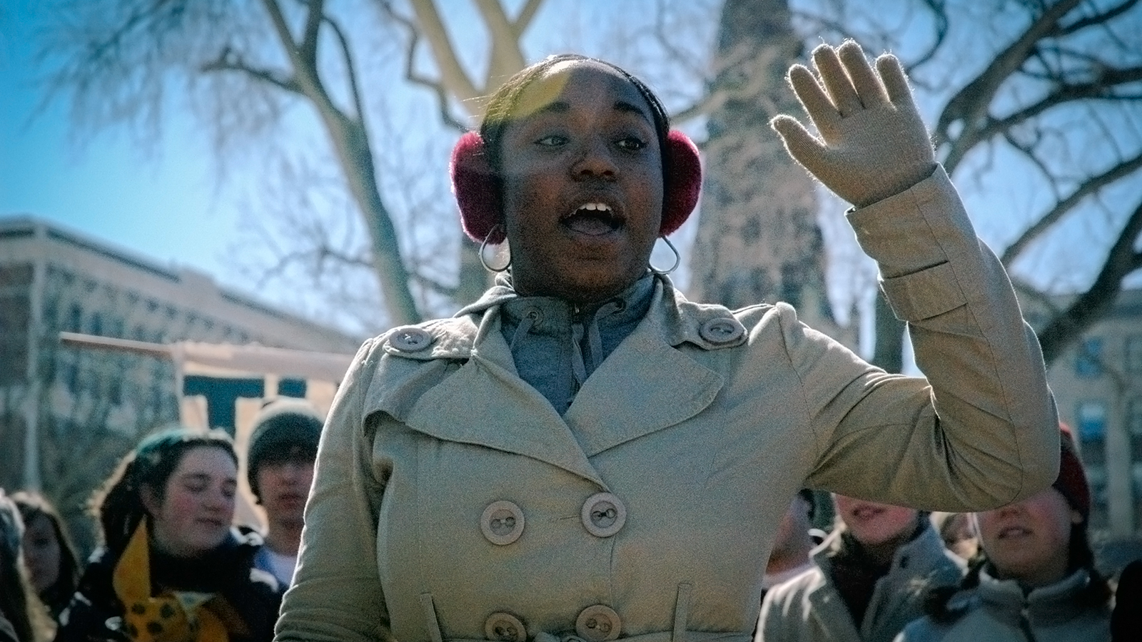 A woman in red earmuffs speaks with one raised against a blue sky with people and trees in the background