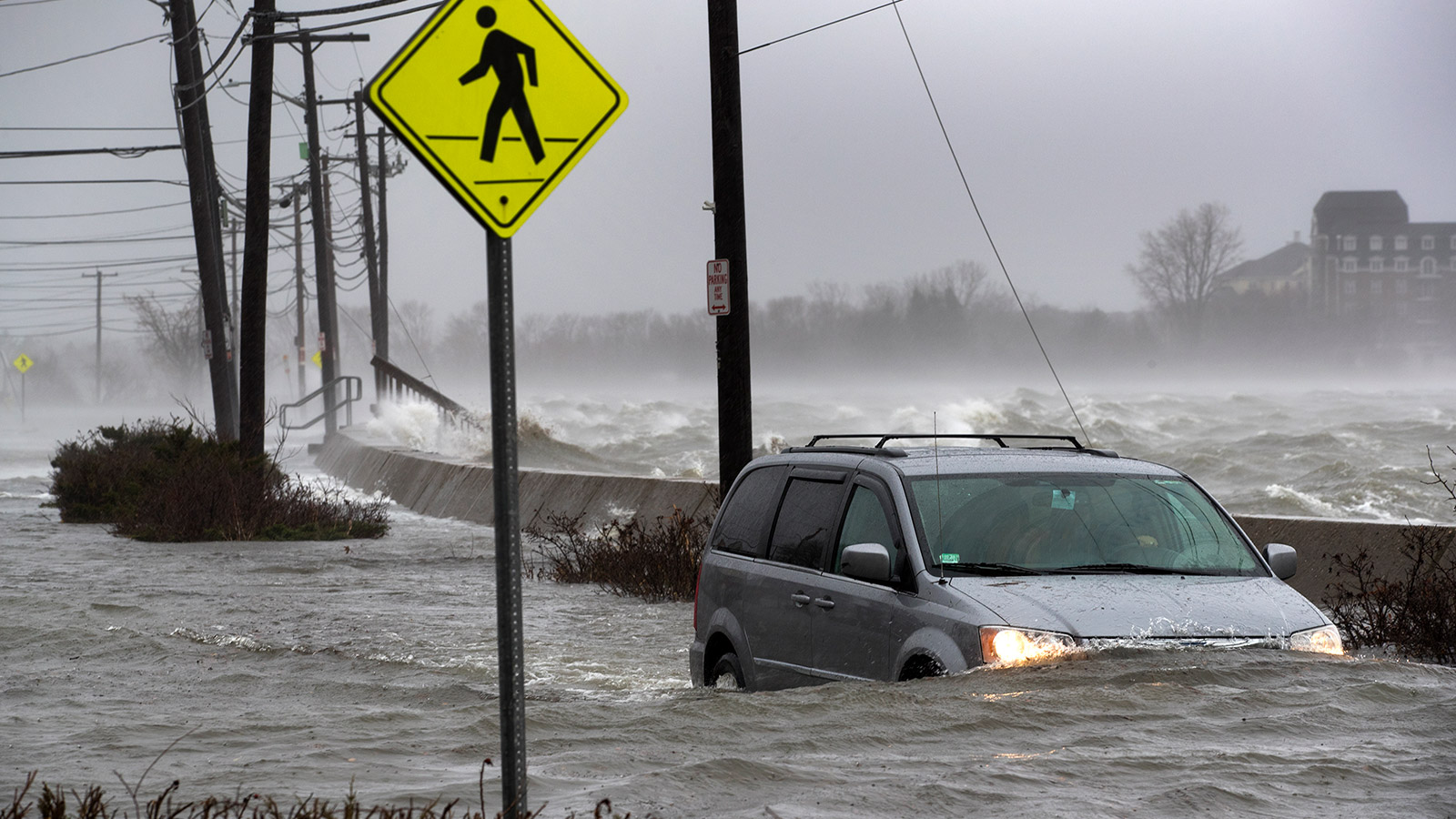 A vehicle navigates a flooded street in the Squantum section of Quincy, MA.