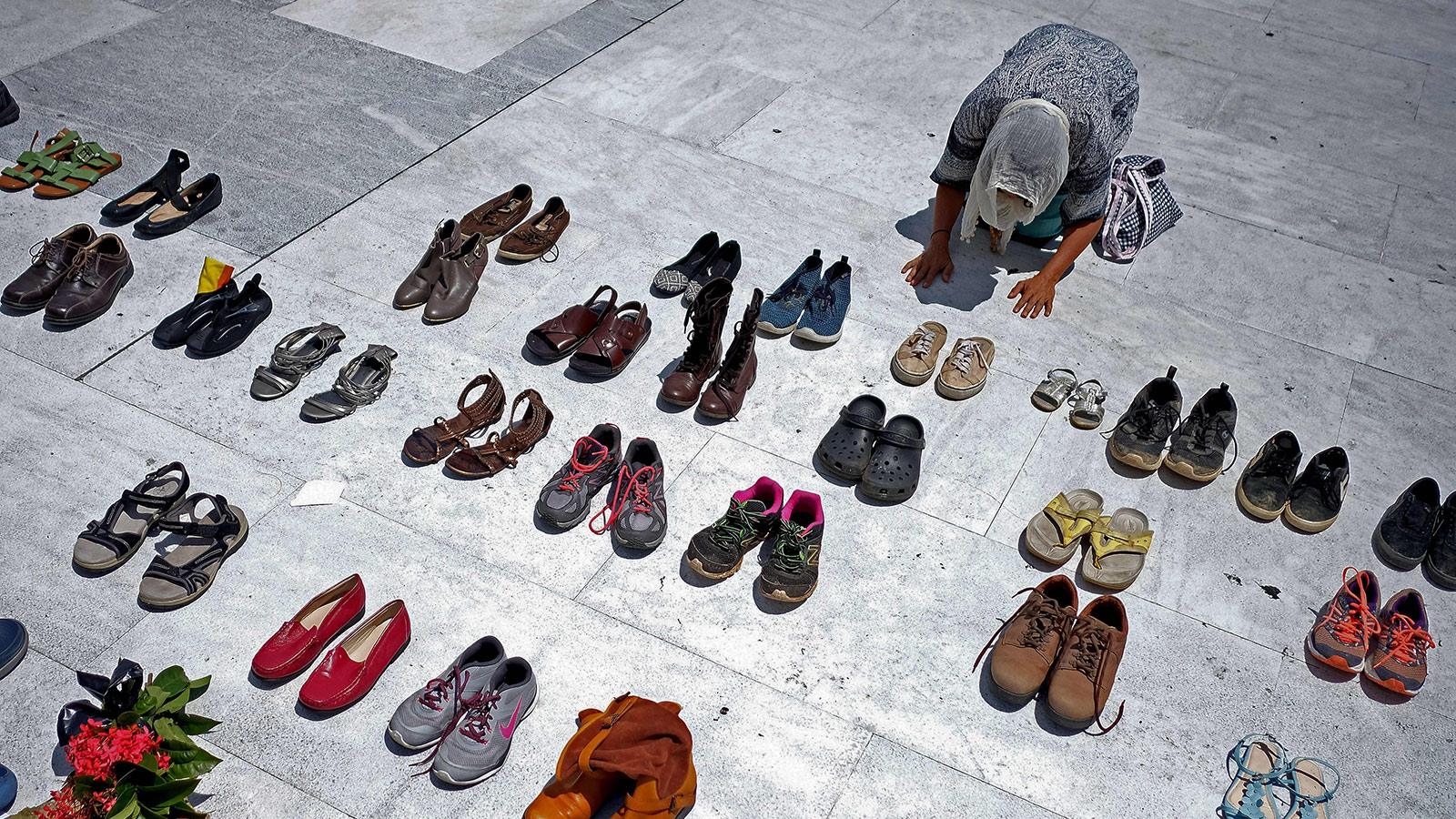 A woman prays in front of hundreds of shoes that were displayed in memory of those killed by Hurricane Maria in front of the Puerto Rican Capitol, in San Juan on June 1, 2018.