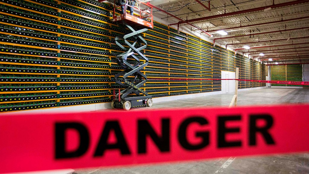 Two construction workers use a lift along a wall of bitcoin mining at Bitfarms in Saint Hyacinthe, Quebec on March 19, 2018. Bitcoin is a cryptocurrency and worldwide payment system.