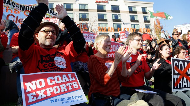 Russ Childers, left, of Seattle, sits among other protesters as they demonstrate against trains carrying coal for export moving through Washington state on Thursday, Oct. 17, 2013, in Tacoma, Wash.