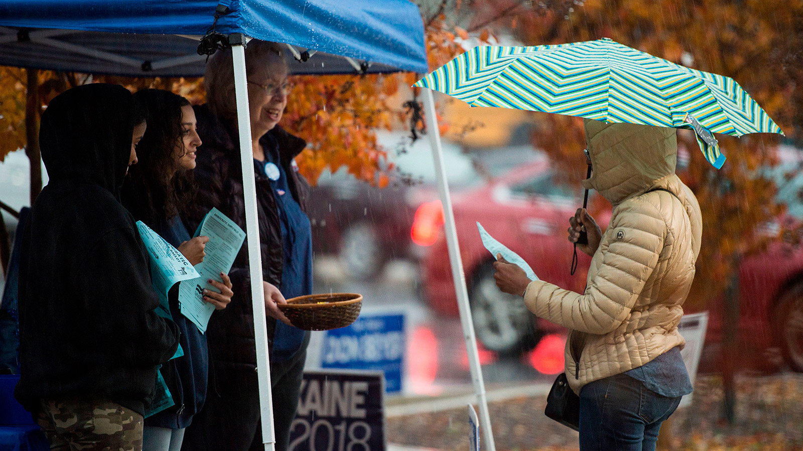 Volunteers with the Democratic party speak to voters outside of a polling station during the mid-term elections at the Fairfax County bus garage in Lorton, Virginia on November 6, 2018.