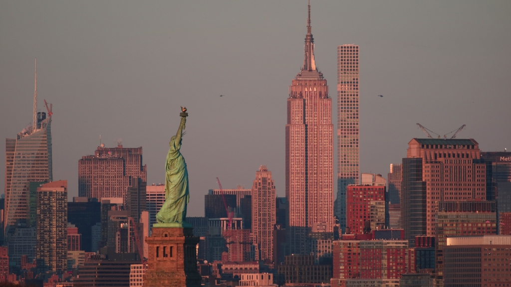 The sun sets on the Empire State Building and Statue of Liberty in New York City.