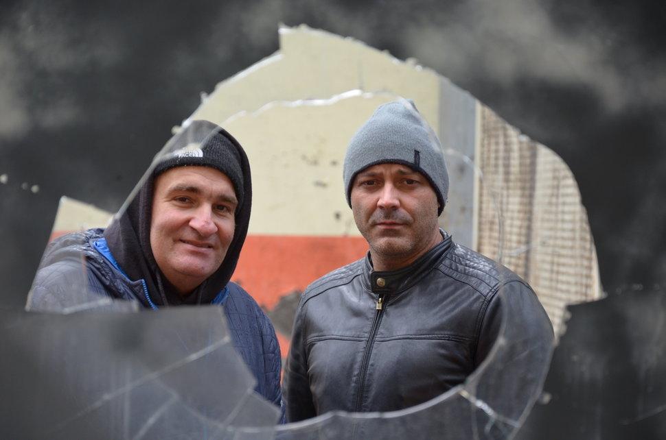 Miners Salvador Osario and Omar Garcia Alvarez look through a window in derelict mine.
