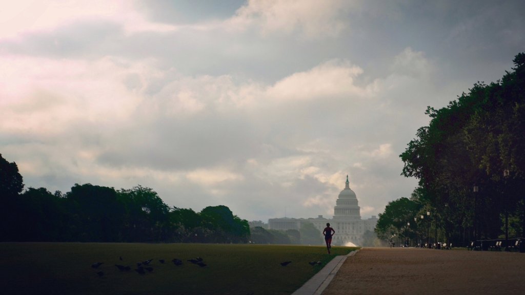 A man runs on a field against a cloudy sky, with the United States Capitol in the background.